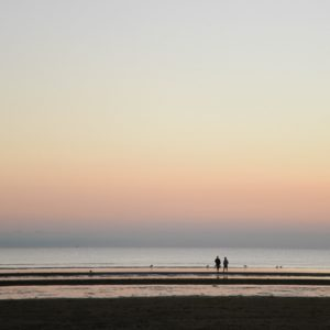 Flat beach, water, dim colors, two people in the distance