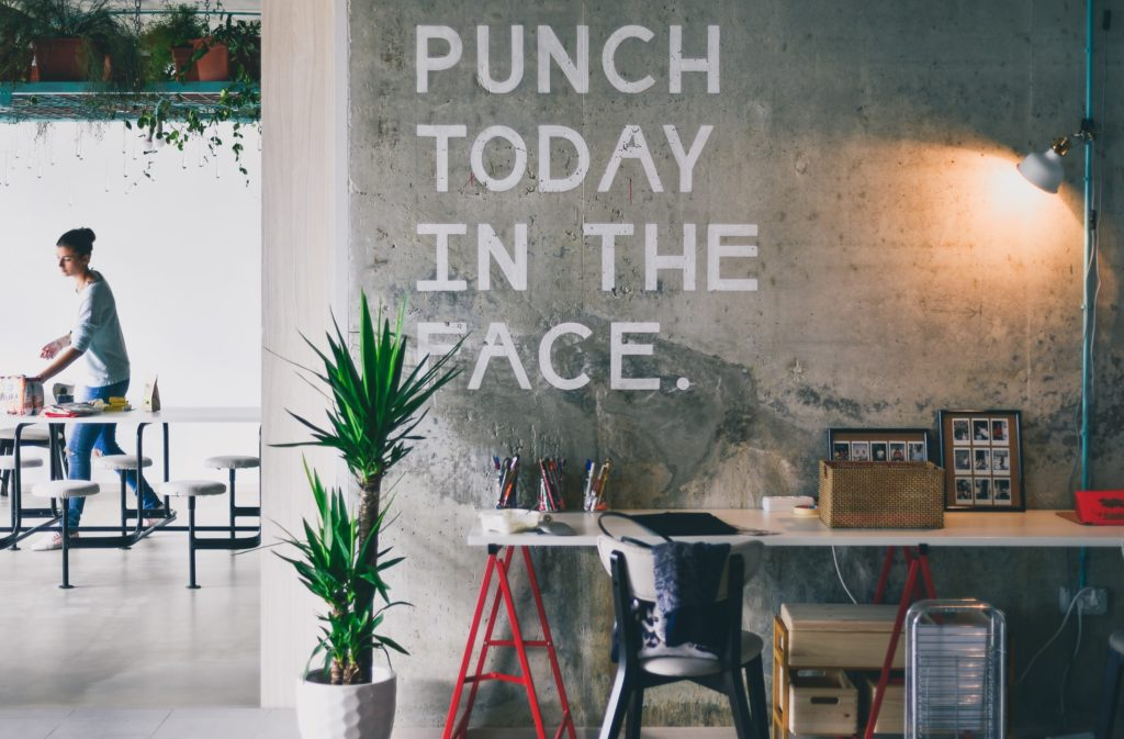 Desk, plant, cement wall that says: Punch today in the face