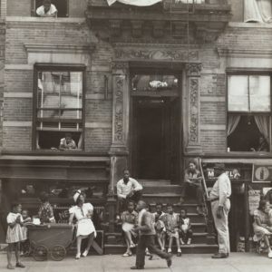 children and adults on a city stoop.Historical image
