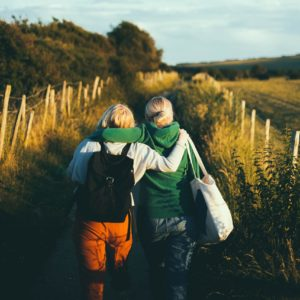 Two people, arms around each other, walking down a trail
