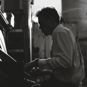 Person playing an upright piano