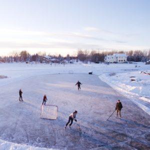 six people playing hockey on ice outdoors