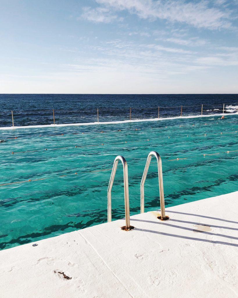 Green swimming pool next to dark blue ocean