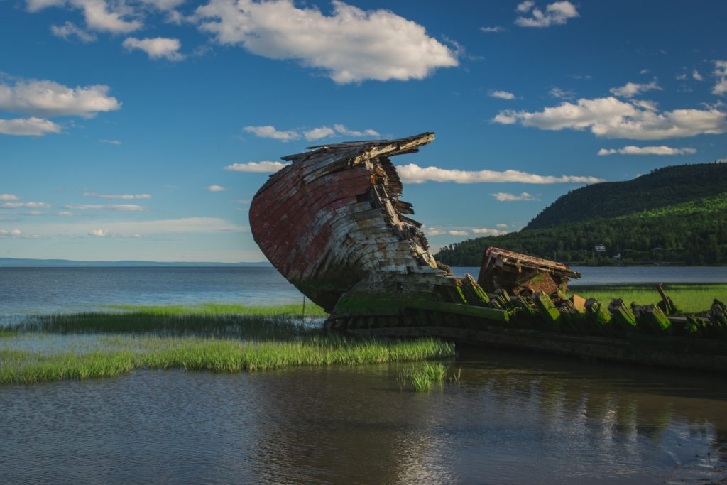 Wooden ship hull jutting improbably out of a placid river landscape
