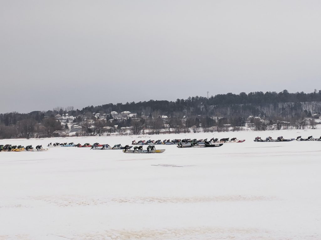 People pushing canoes down a frozen river