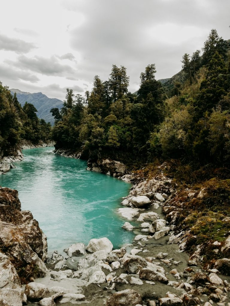 blue-green water flows through a rocky river bed